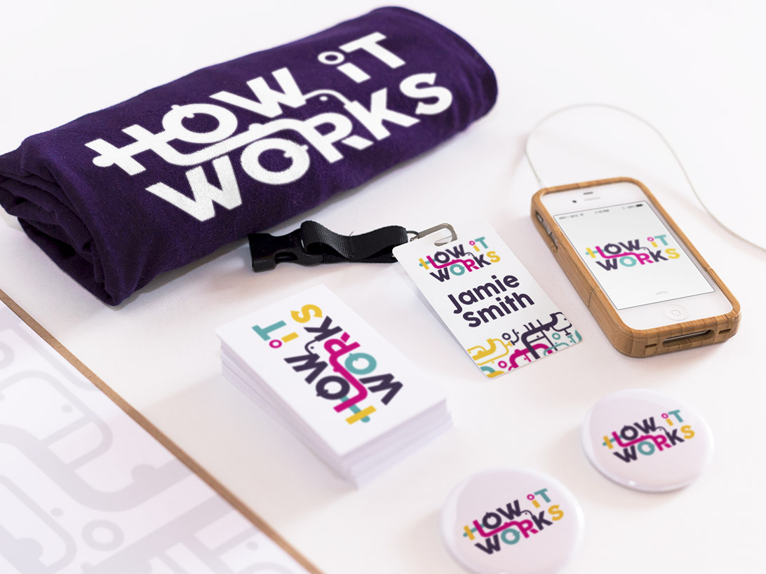 How it Works logo on a T-shirt, name badge, buttons, business cards, and an iPhone