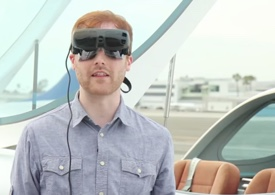 Photo of man wearing eSight with a plane behind him