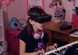 Photo of Emma-Rose wearing eSight and playing piano