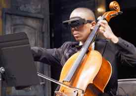 Photo of Nicholas wearing eSight and playing the cello