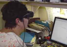 Photo of Leslie wearing eSight using the computer