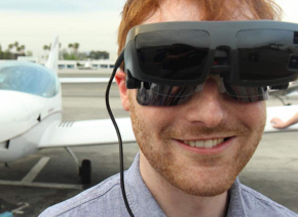 Man smiling and wearing eSight in front of a plane
