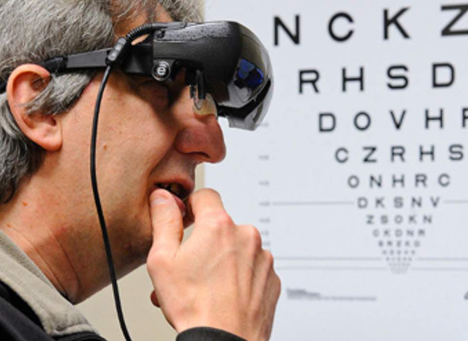 Man wearing eSight with hand on chin and eye chart in the background