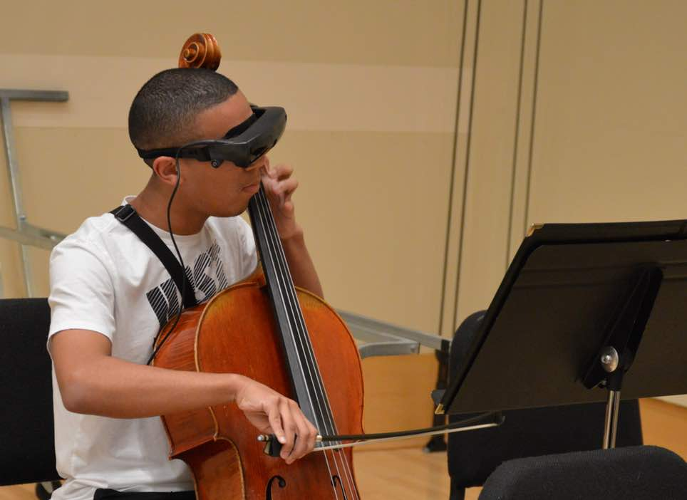 Young man playing the cello and wearing eSight