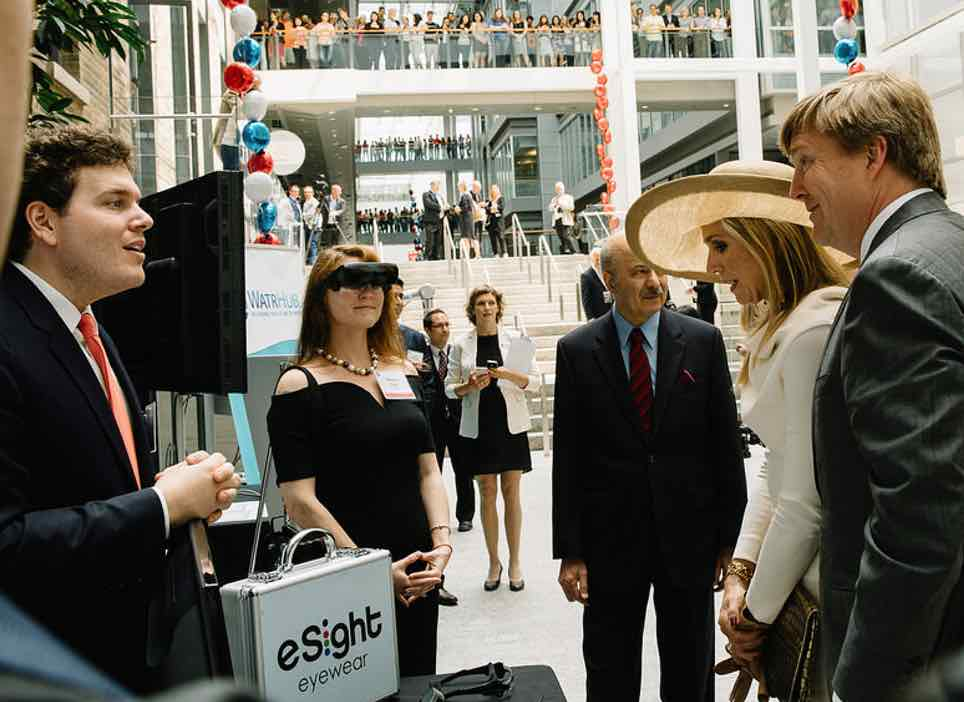 Man and woman presenting eSight to the dutch royal family in a large atrium