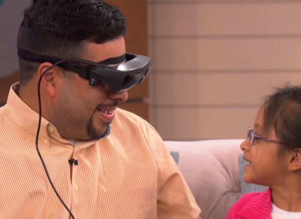 Man wearing eSight and looking at his daughter with amazement