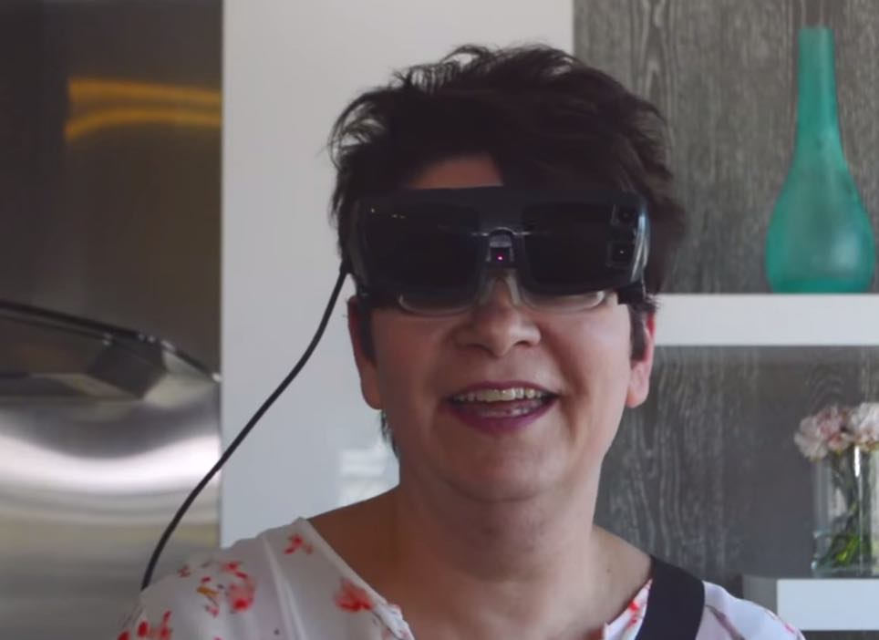 Woman wearing eSight and smiling in her kitchen
