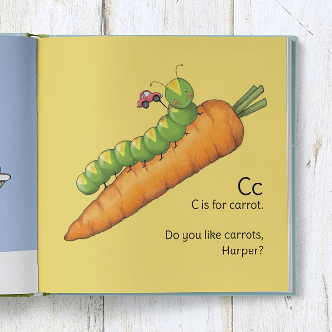 C is for carrot page of the personalized ABC book features an illustration caterpillar holding a car while inching up a large carrot.  The page is personalized with the child's name in the form of a question (do you like carrots <insert child's name>?)