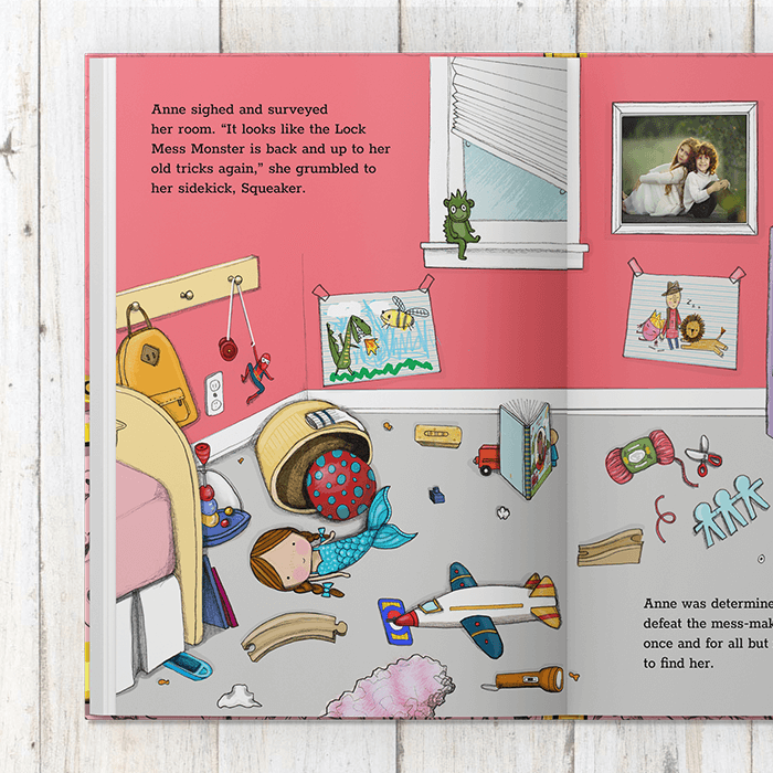 A pink child's bedroom with a bed and artwork on the walls.  Toys are haphazardly strewn about on the floor.  Book text references child's name in several places