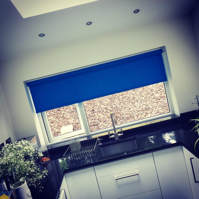 blue roller blind fitted in kitchen against white backdrop