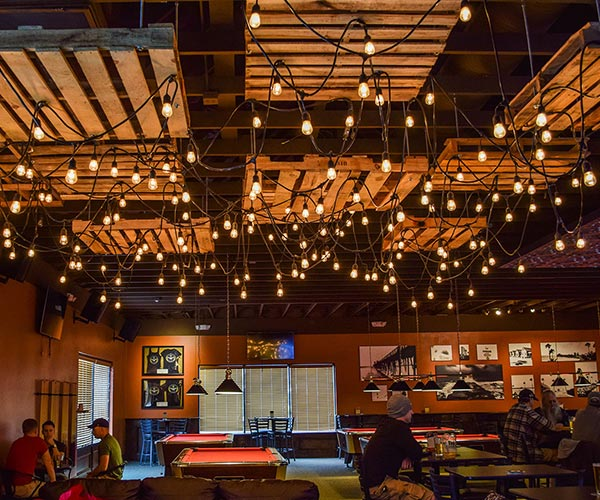Wide shot photo of a bar with bistro lights hanging from the ceiling.
