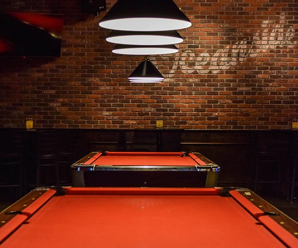 Photo of pool tables in front of an exposed brick wall.