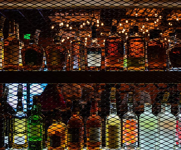 Photo of liquor bottles behind a bar.