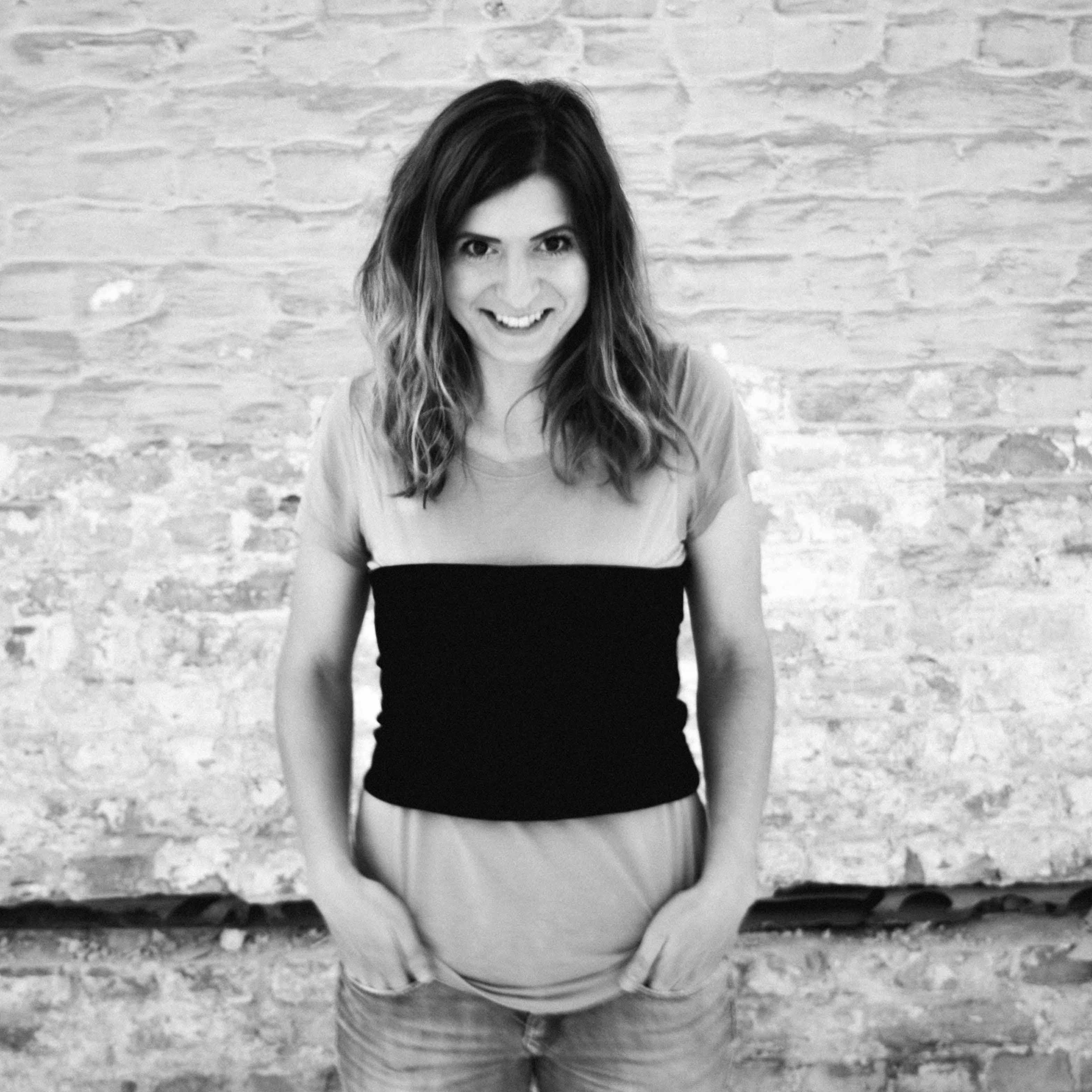 Portrait der Mode Stylistin in schwarz- weiß gestylt in handgemachtem Bandeau Top, lachend an einer Backsteinwand.
